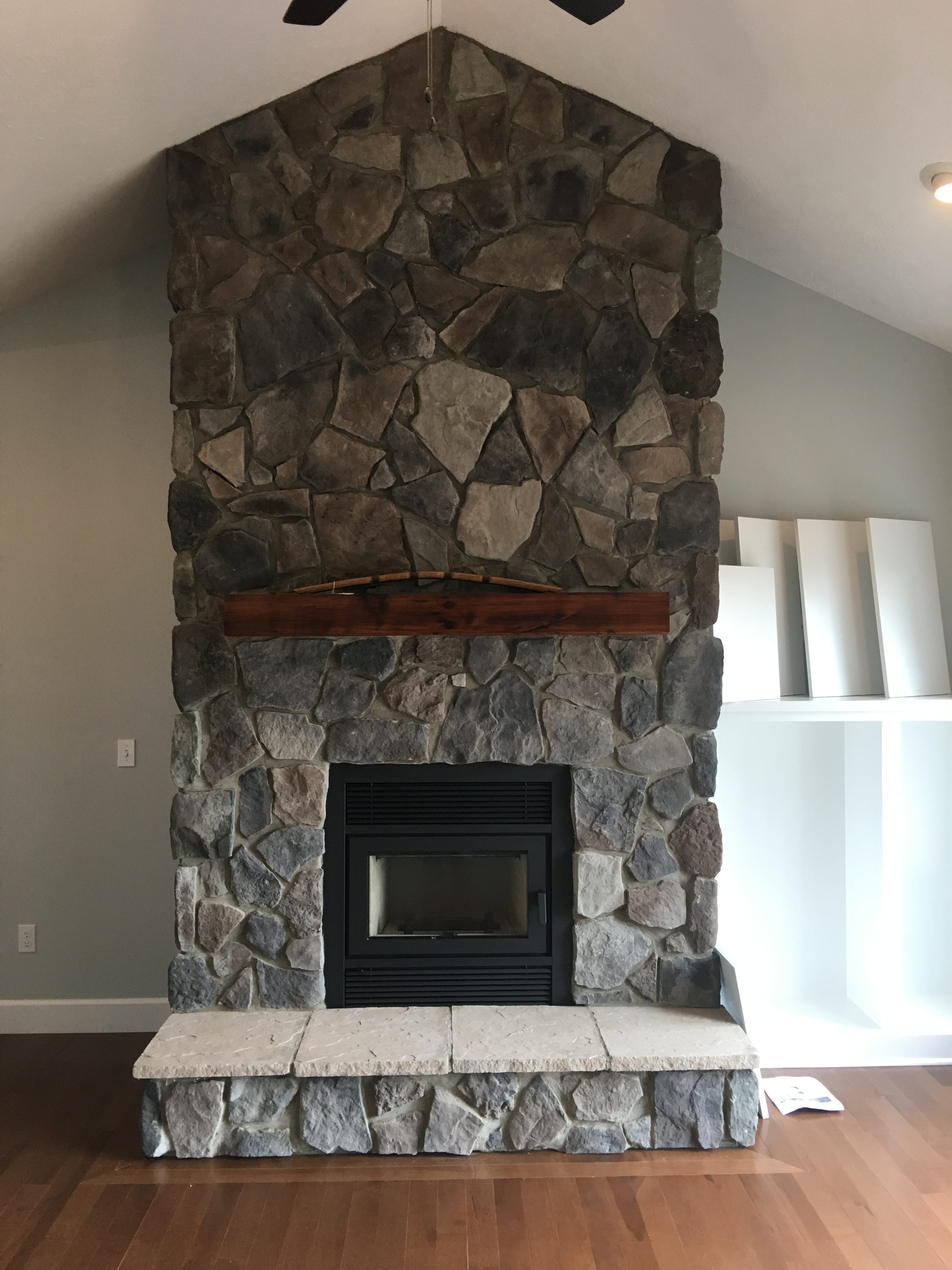 Image of a traditional Brentwood wood fireplace by Astria featuring rustic stonework facing and mantle.