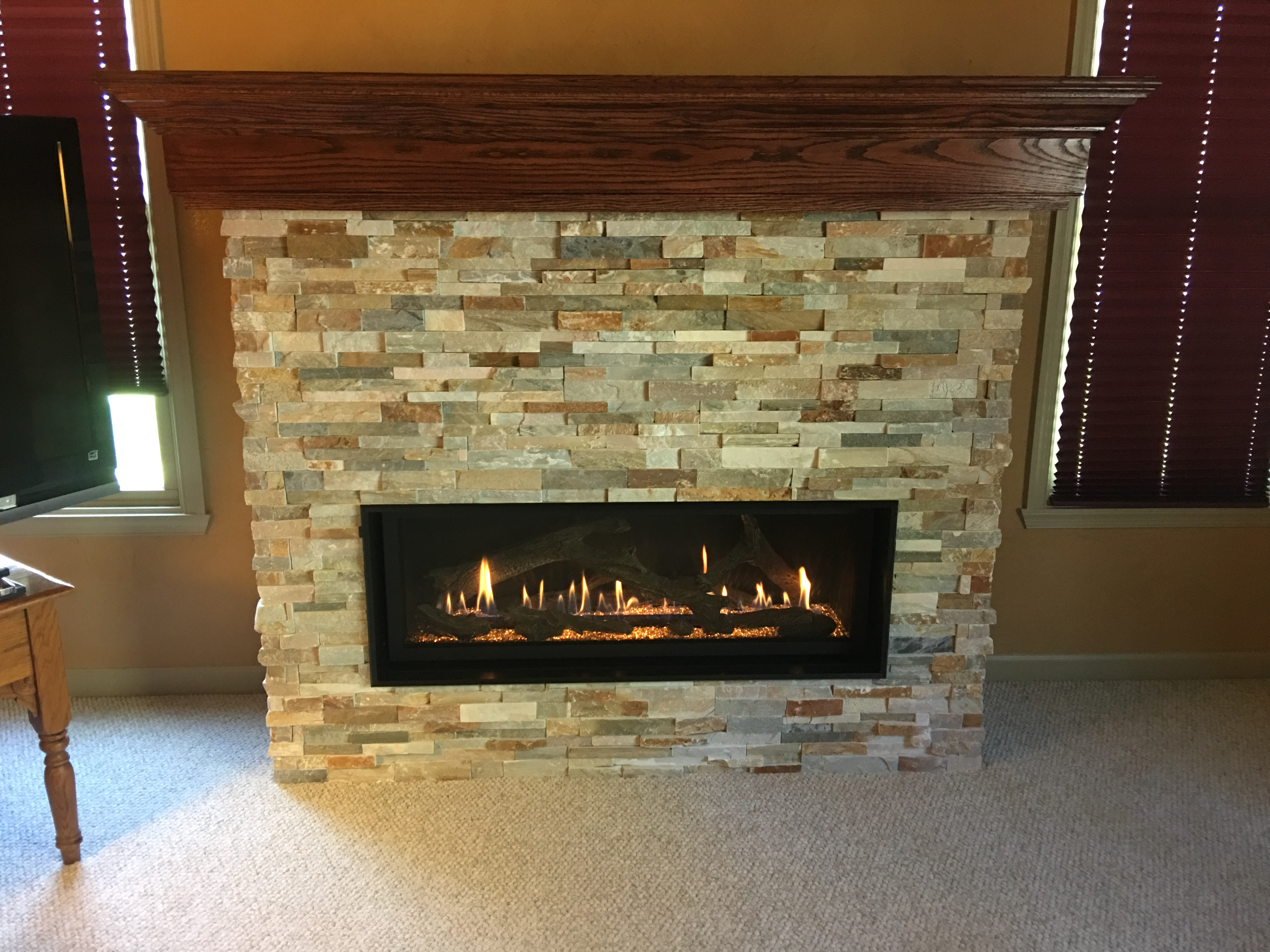 Image of a contemporary 4415 HighOutput gas fireplace by Fireplace X featuring tile facing and mantle.