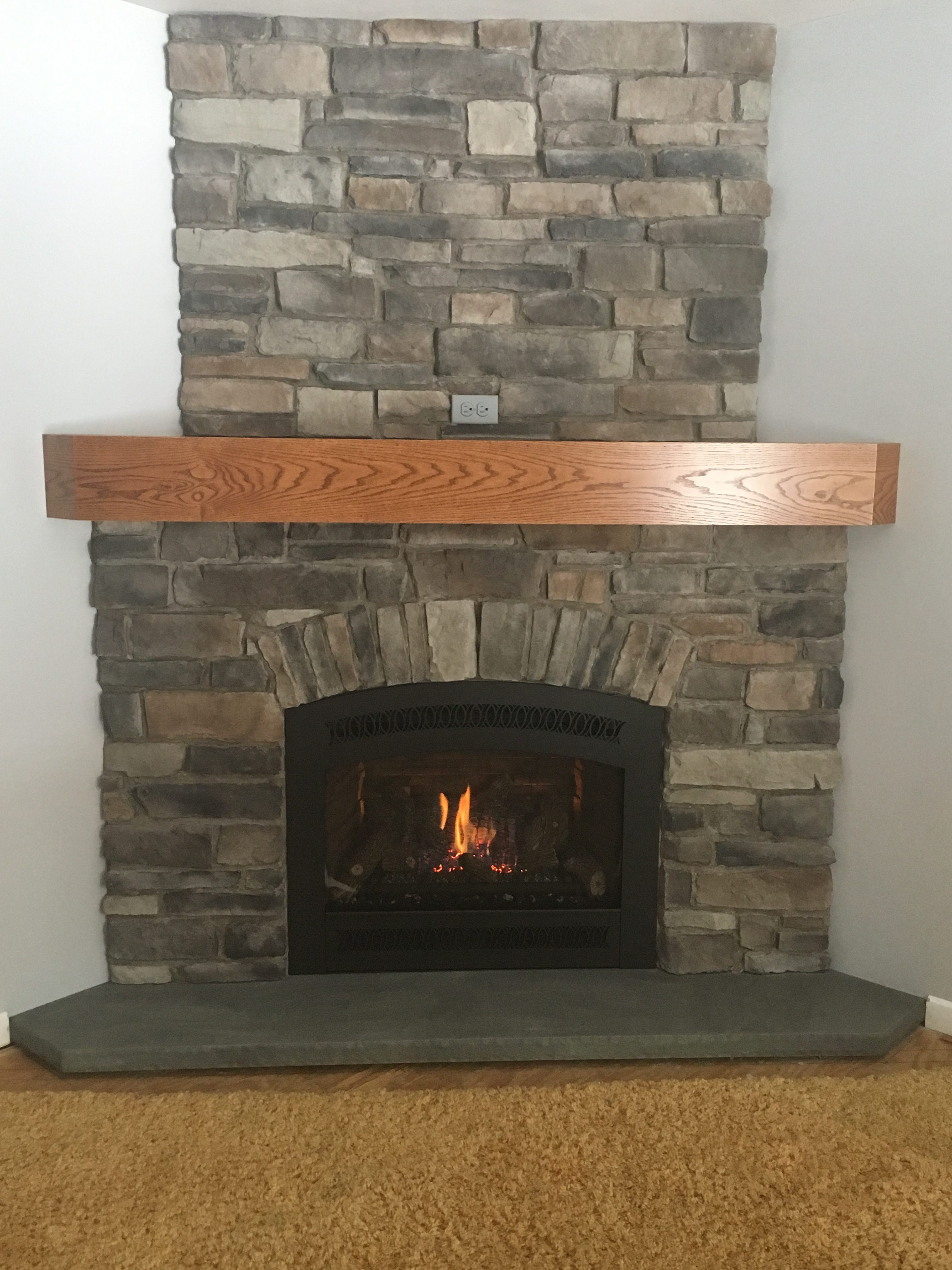 Image of a traditional 564 HighOutput gas fireplace by Fireplace X featuring rustic stonework facing and mantle.