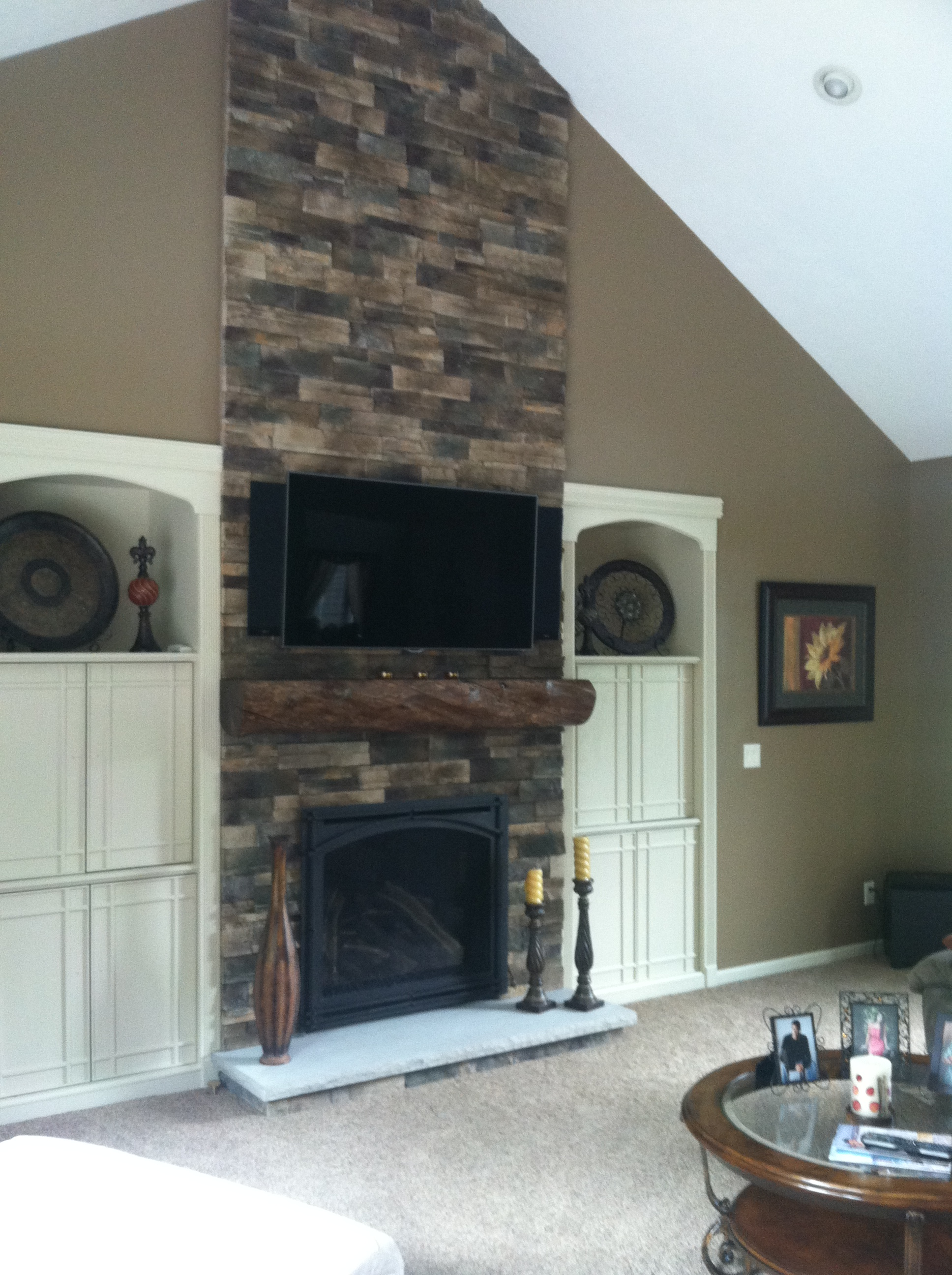 Image of a traditional Carlton 39 gas fireplace by Kozy Heat featuring rustic stonework facing and built in cabinets.