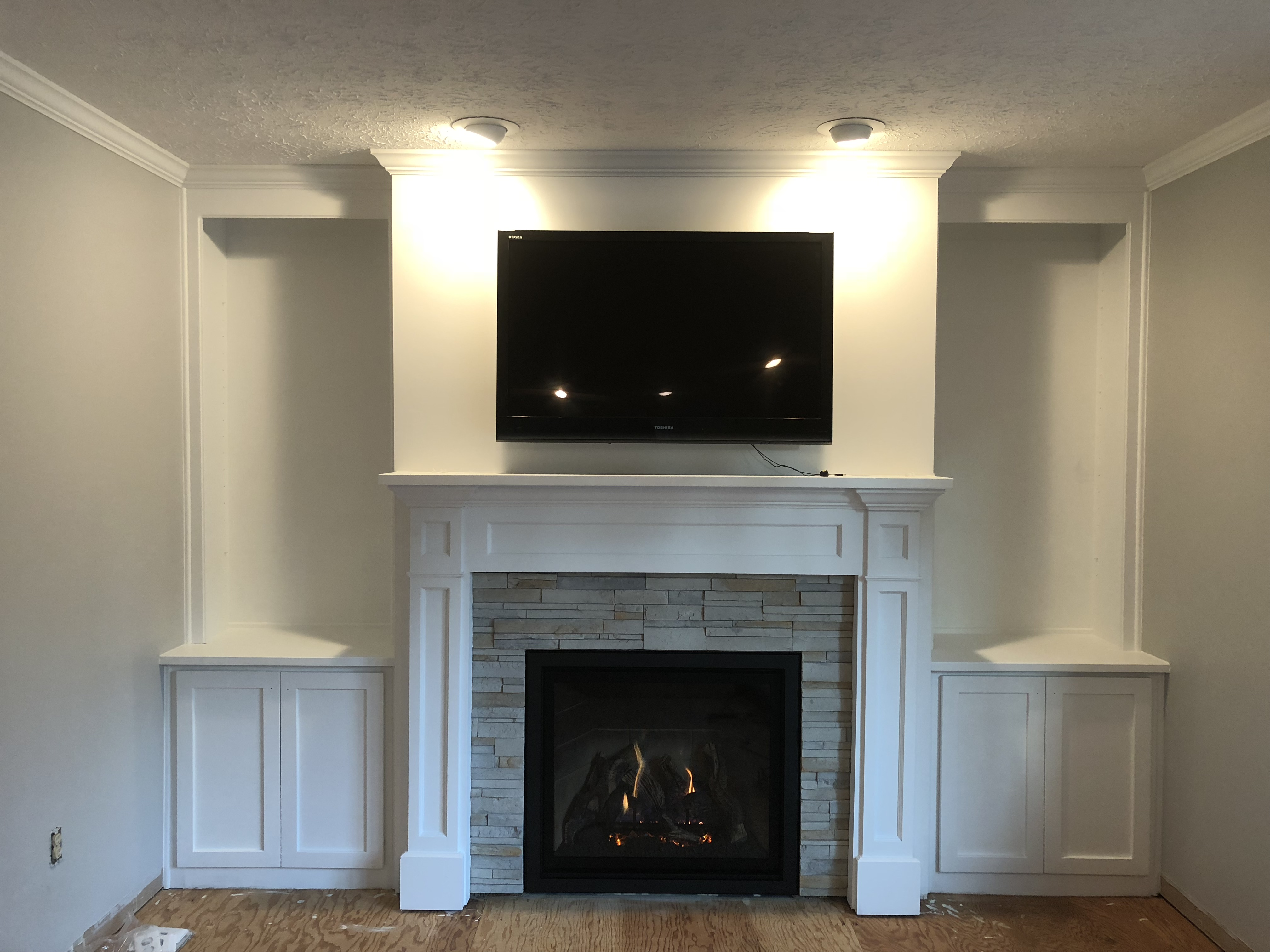Image of a traditional Bayport 36-L gas fireplace by Kozy Heat featuring stone facing and painted mantle and built ins.