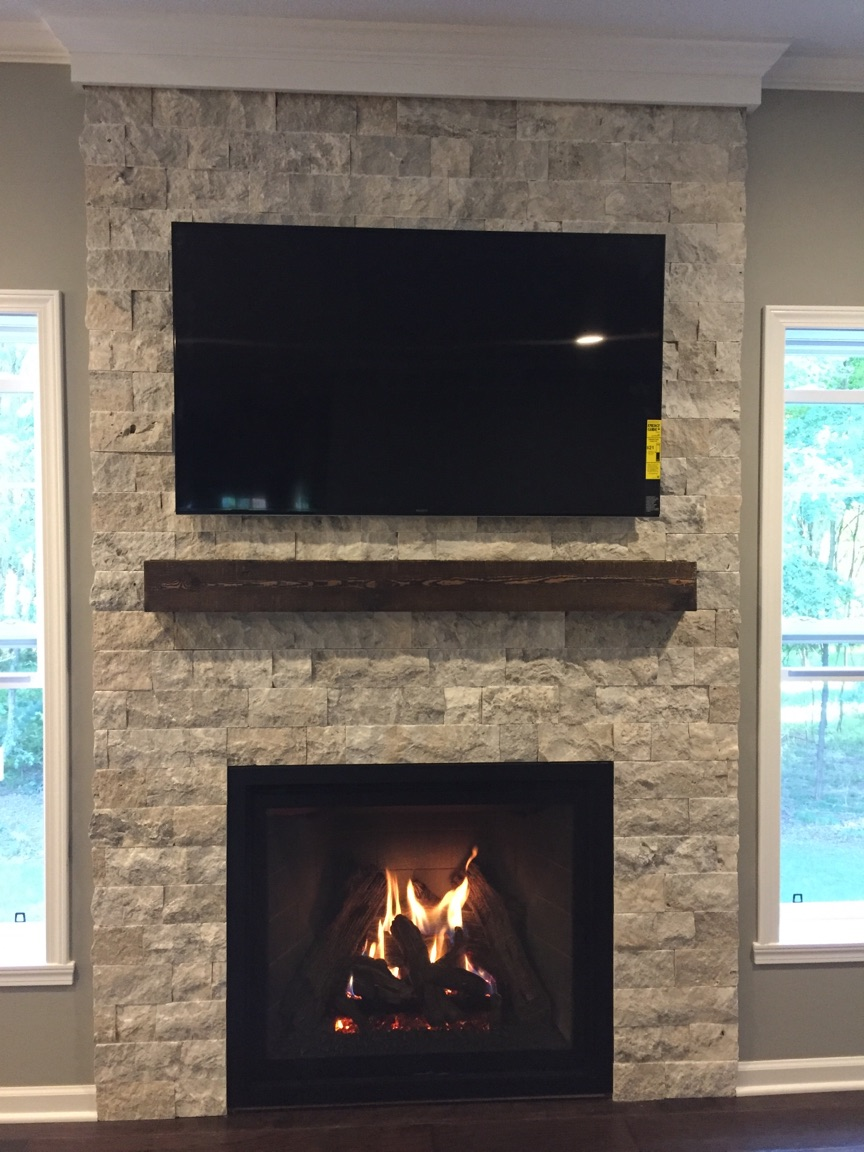 Image of a sleek Carlton 39 gas fireplace by Kozy Heat featuring stone facing and mantle.