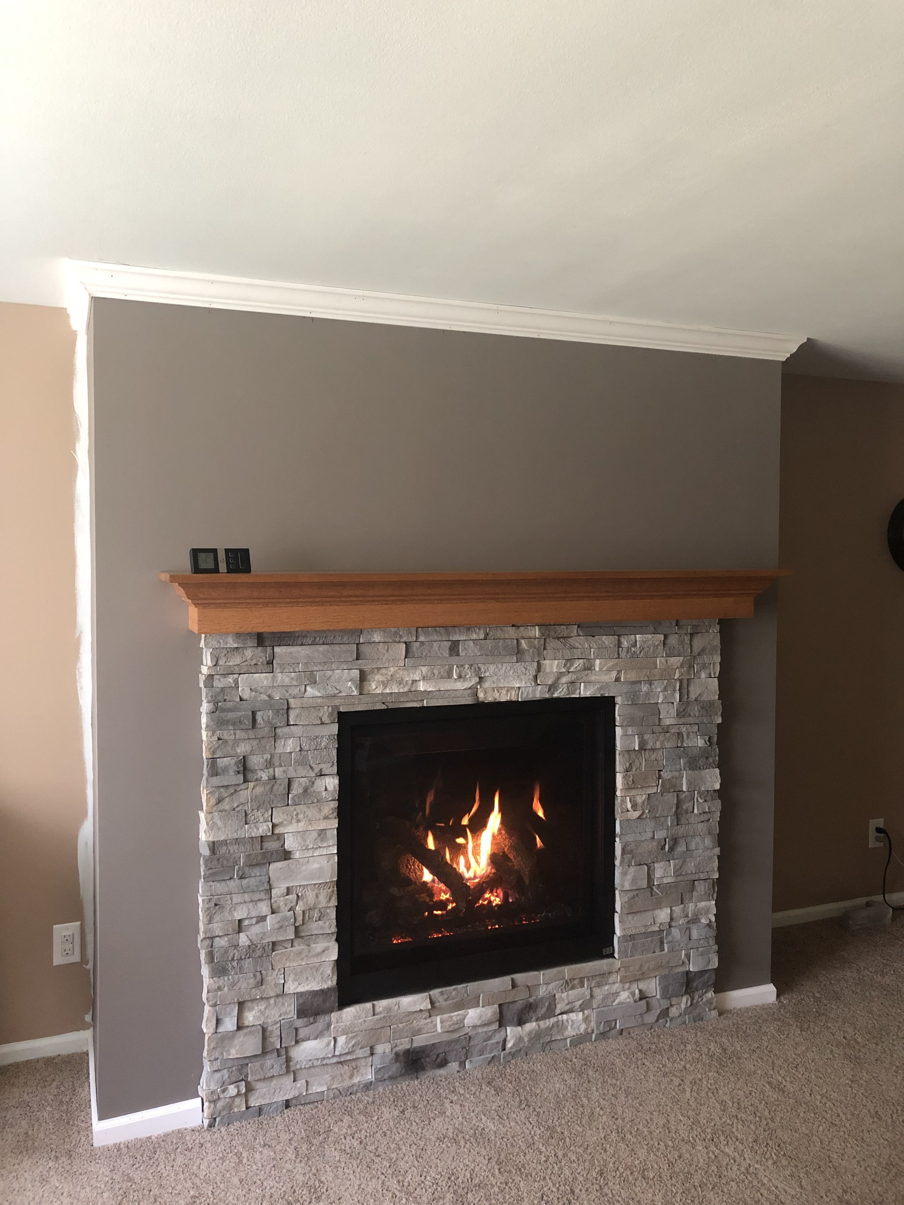 Image of a Probuilder 36CF Gas fireplace by Travis Industries featuring reflective ceramic black glass interior and stone facing.