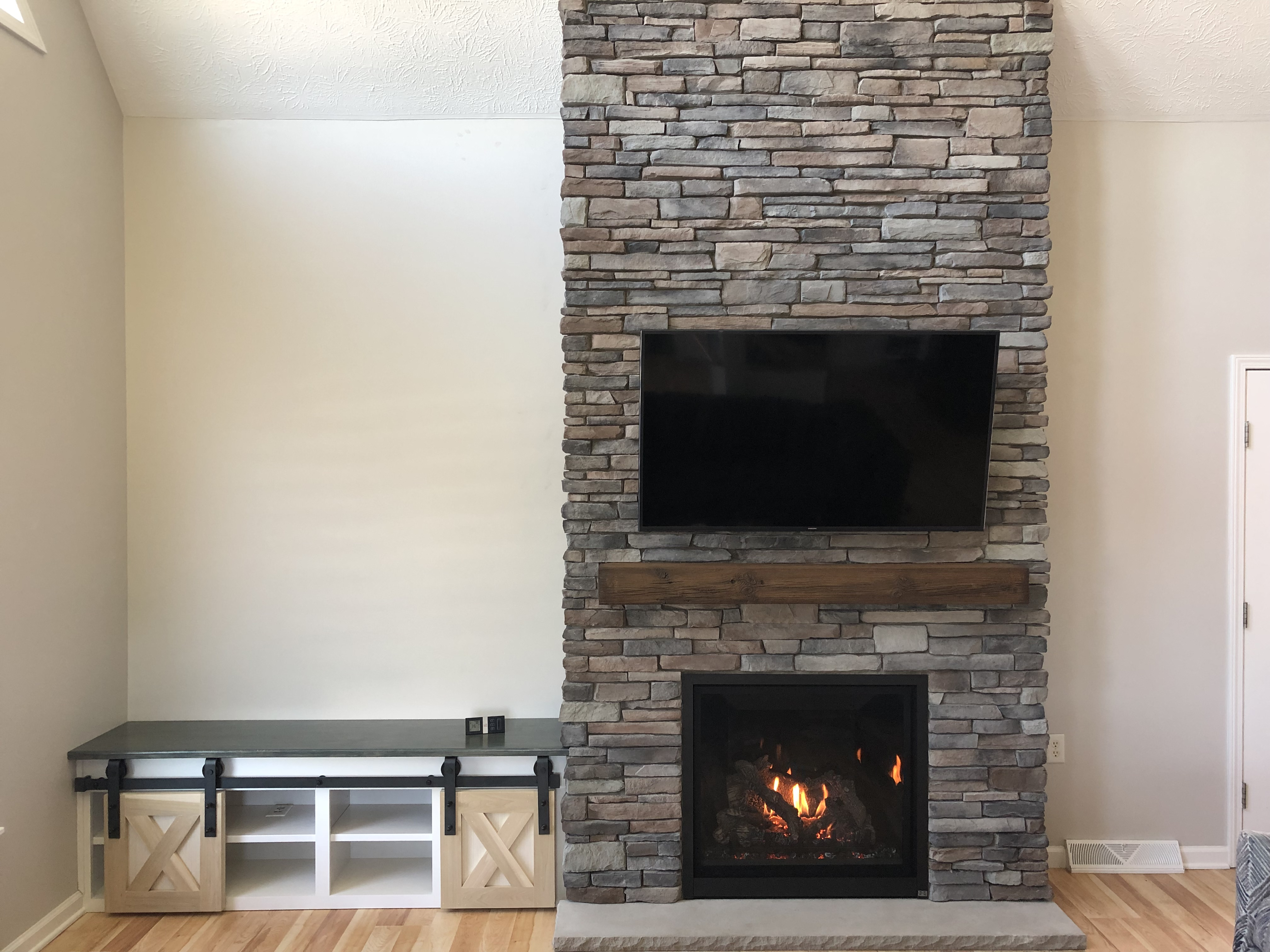 Image of a Probuilder 36CF Gas fireplace by Travis Industries featuring reflective black glass interior and Rustic Beam MagraHearth Mantle.